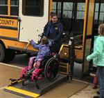 Bus Driver loading student in Wheelchair