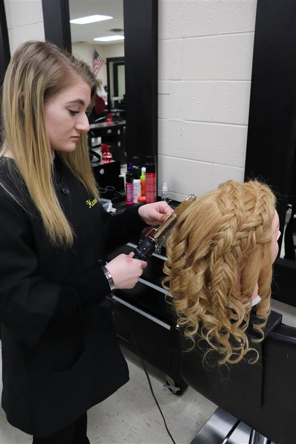 Cosmetology student working on mannequin head